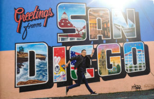 Kevin dances salsa in from of a San Diego mural
